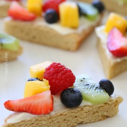Need a colorful dessert idea for Mother's Day? Try these lightened up white chocolate cookie bars topped with cream cheese frosting and fresh fruit. The perfect dessert for Spring or Summer!