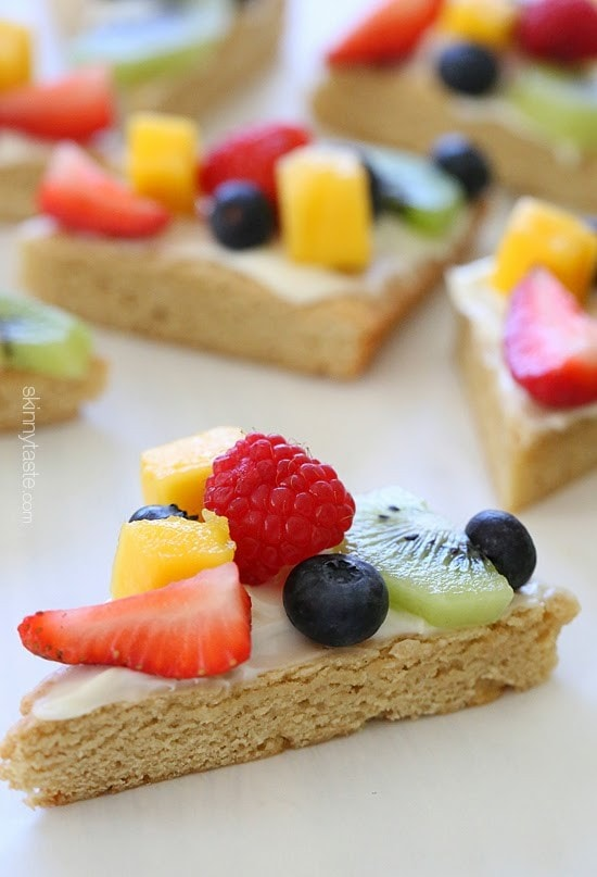 This easy healthy fruit pizza is lightener sugar cookie with white chocolate chips topped with cream cheese frosting and fresh fruit. The perfect rainbow dessert for Mother's Day, Spring or Summer!