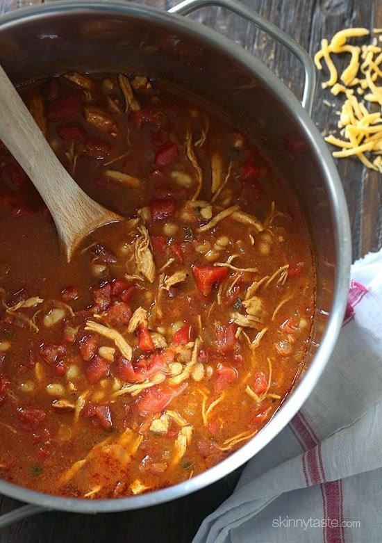 A pot of BBQ chicken chili with a wooden spoon