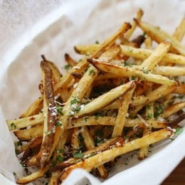 These delicious fries are baked in the oven with garlic, a little olive oil, kosher salt and black pepper, then sprinkled with freshly grated Parmesan and parsley – to die for!