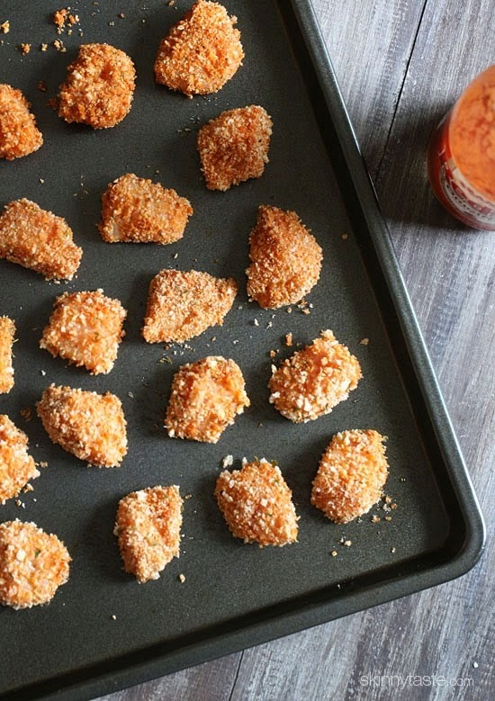 A baking sheet with uncooked breaded chunks of chicken.