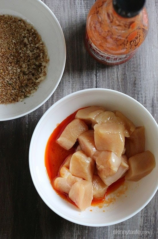 A bowl of cubed raw chicken with hot sauce and a bowl of breading mixture.