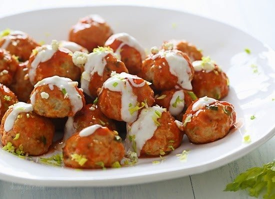 Perfect for football season! Baked chicken meatballs with minced celery and carrots hidden inside, topped with hot sauce, and homemade blue cheese dressing – yum!