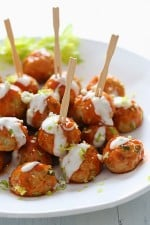 Buffalo Chicken Meatballs are perfect for football season! Made with minced celery and carrots hidden inside, topped with hot sauce, and homemade blue cheese dressing – yum!