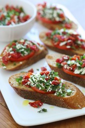 Super easy two tomato bruschetta made with roma and sun dried tomatoes, basil and feta cheese over toasted whole wheat bread.