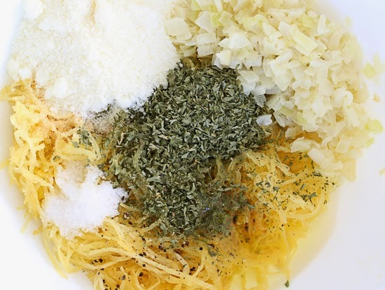 A mixing bowl with cooked spaghetti squash, diced onion, grated Pecorino Romano cheese, and dried herbs
