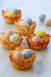 Coconut macaroons shaped like a bird's nest, filled with mini chocolate Cadbury eggs. An tasty Easter treat!