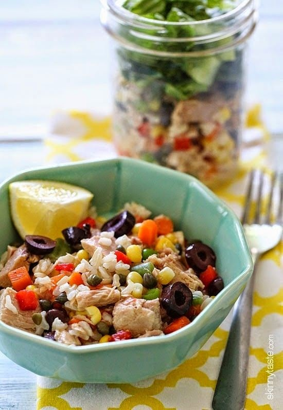 A bowl of rice mixed with chunks of canned tuna, colorful mixed vegetables, sliced olives, and a lemon wedge.