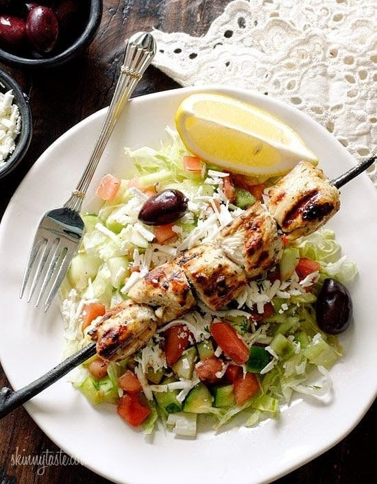 A plate of shredded lettuce, kalamata olives, diced cucumbers and tomatoes, grated feta, and a skewer with chunks of grilled chicken on top.
