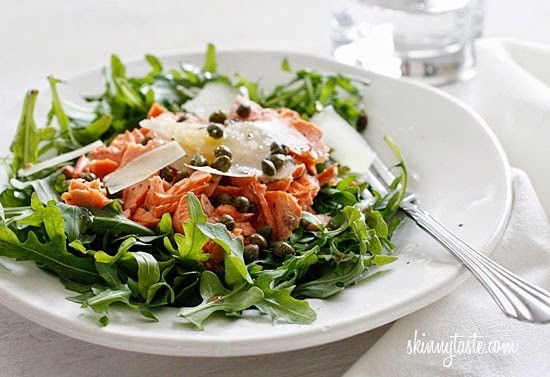 A plate of arugula topped with pieces of salmon, capers, and shaved Parmesan cheese.