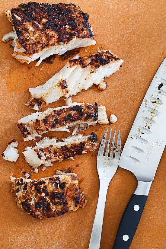 A cutting board with blackened grilled white fish cut into a few slices