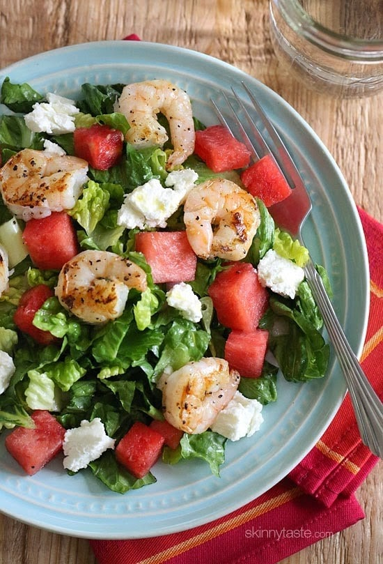 A bowl of romaine lettuce topped with diced watermelon, crumbled goat cheese, and grilled shrimp.