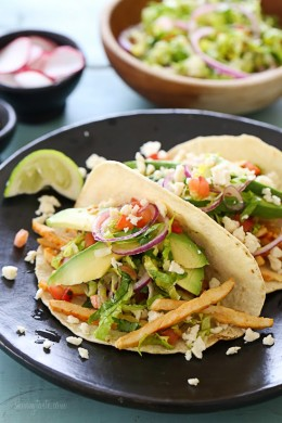 Grilled chicken tacos piled high with a lettuce-tomato slaw, avocado, and Cotija cheese all served on a charred tortilla. A quick weeknight dinner solution!