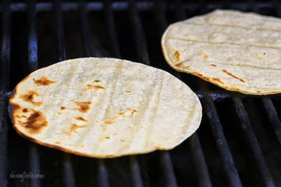 Two corn tortillas on a grill