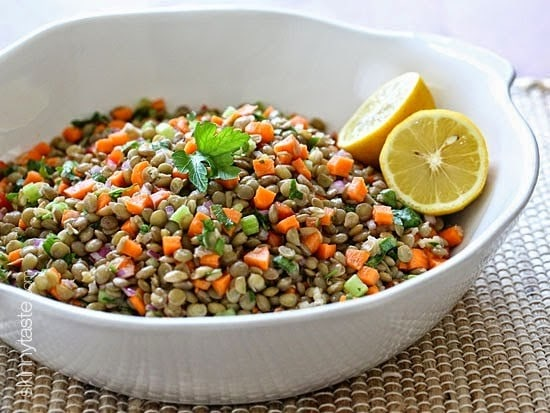 A bowl of lentils mixed with diced carrots, onions, bell peppers, topped with fresh parsley and lemon halves.