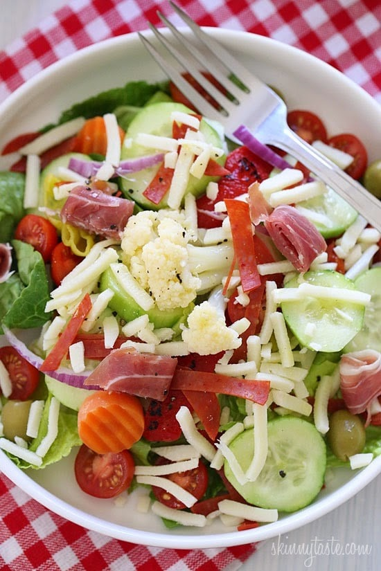 A bowl of antipasto salad with lettuce, tomato, cucumber, roasted red peppers, pepperoncini, sliced italian meats and shredded cheese.