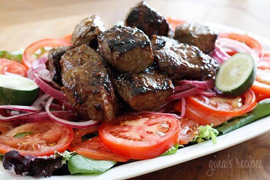 A plate of salad greens topped with sliced tomatoes, sliced red onion, and chunks of grilled steak.