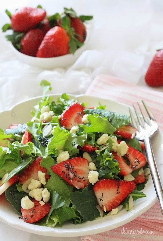 A bowl of leafy greens topped with sliced strawberries, slivered almonds, crumbled gorgonzola cheese, and poppy seed dressing.