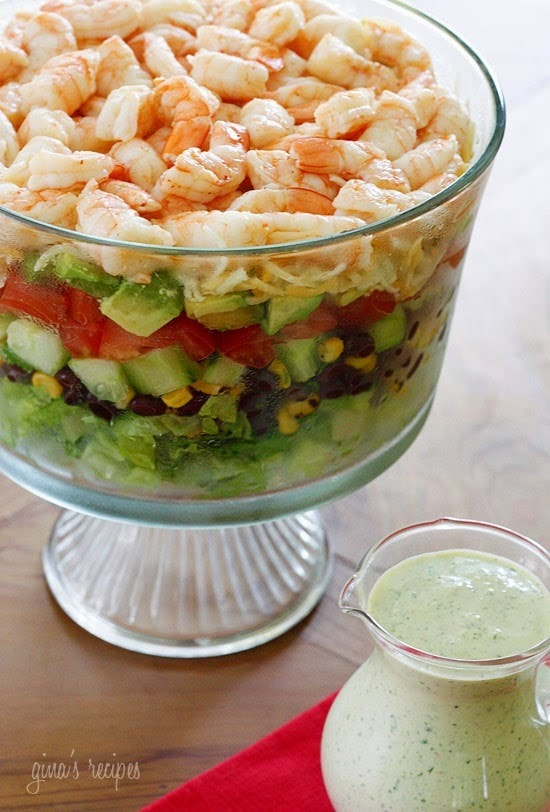 A trifle bowl filled with a layered salad containing chopped lettuce, black bean salsa, corn, diced cucumbers, diced tomatoes, diced avocado, shredded cheese and grilled shrimp, served with creamy cilantro dressing.