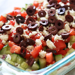 Hummus, yogurt, red onion, cucumbers, tomatoes, feta and olives are layered to create this delicious Greek inspired dip – grab a chip and serve this at your next party!