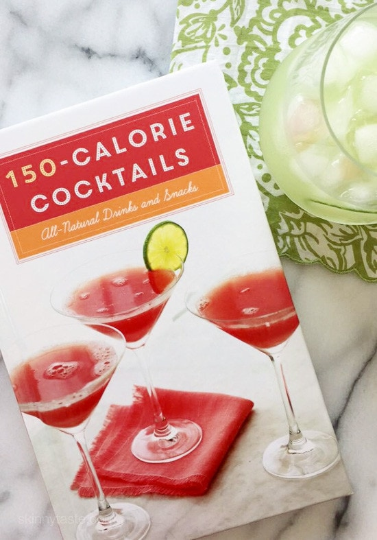 A book titled 150-calorie Cocktails and a glass filled with Basil Cucumber Cooler cocktail with ice