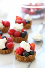 Perfect summer treat, these tartlets are made with a graham cracker crust, drizzled with dark chocolate and filled with fresh berries