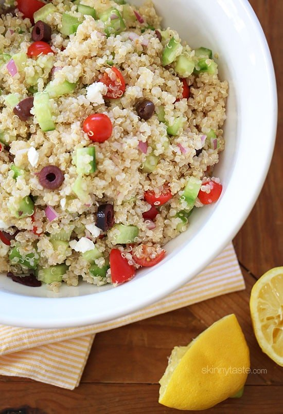 A bowl of quinoa salad with diced cucumber, grape tomatoes, kalamata olives, red onion, and feta cheese.