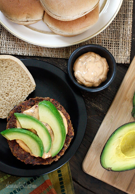 A plate with a black bean burger patty with creamy spread and sliced avocado on an open bun.
