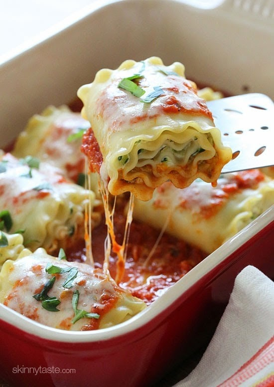 A casserole dish of rolled lasagna noodles filled with shredded zucchini and cheese, topped with marinara sauce and melted cheese.