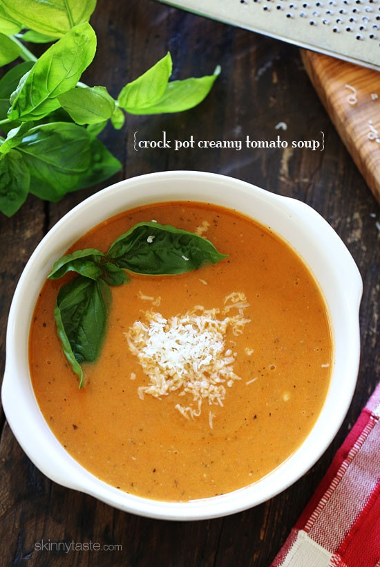 A bowl of creamy tomato soup with basil leaves and grated Parmesan cheese on top.