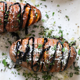 These sweet potatoes are sliced and roasted in the oven, then drizzled with balsamic and topped with parmesan and fresh herbs.