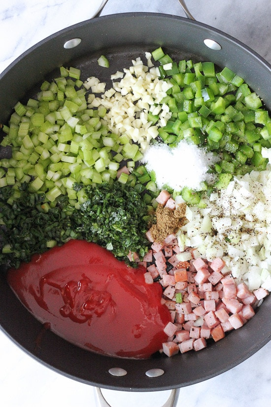 Raw diced veggies, spices and tomato sauce, uncooked in a pot.