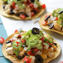 """These easy loaded chicken """"nacho"""" tostadas – topped with cheese, tomatoes, guacamole, olives and jalapenos are a great way to take nachos and turn them into a main dish."""