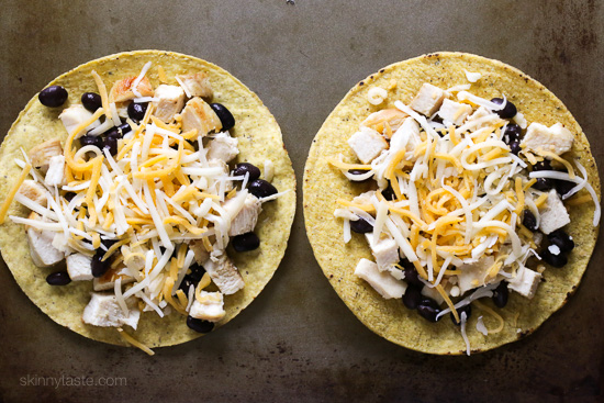 "These easy loaded chicken ""nacho"" tostadas – topped with cheese, tomatoes, guacamole, olives and jalapenos are a great way to take nachos and turn them into a main dish."