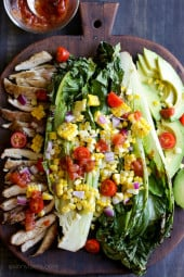 An EASY 15-minute dish you'll want to make all summer long! Fresh heads of romaine lettuce are split down the middle, grilled until slightly charred and smoky, along with fresh corn and skinless chicken thighs, then topped with tomatoes, onions, avocado and a simple salsa vinaigrette.