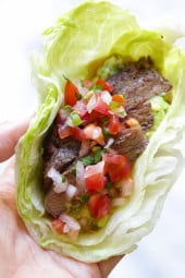 "Grilled sirloin steak ""flaco"" tacos use lettuce wraps instead of tortillas! The steak is seasoned with cumin and spices, then grilled and sliced thin, along with guacamole and pico de gallo – low-carb and super delicious!"