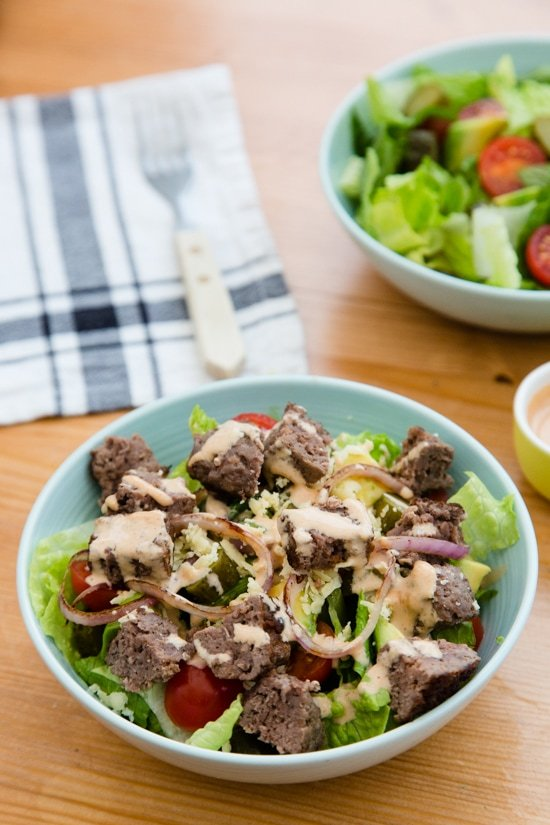This salad has everything I love about a cheeseburger, sans the bun. Chopped romaine, tomatoes, avocado, pickles, shredded cheese topped with grilled burgers, red onions and drizzled with a seriously delicious dressing.