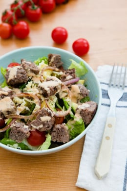 This salad has everything I love about a cheeseburger, sans the bun. Chopped romaine, tomatoes, avocado, pickles, shredded cheese topped with grilled burgers,red onions and drizzled with a seriously delicious dressing.