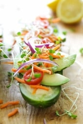 Cucumbers with the seeds scooped out and filled with hummus, avocado, tomatoes, onion and sprouts. So refreshing, healthy and light! An easy low-carb, low-sodium, gluten-free alternative to bread.