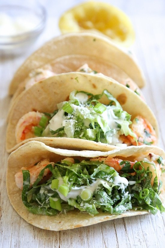 Shrimp Scampi Tacos with Caesar Salad Slaw, a unique twist on a shrimp taco! The shrimp is sauteed with butter and lemon juice topped with Caesar salad slaw and served in tortillas, so fresh and light and takes less than 20 minutes to make!