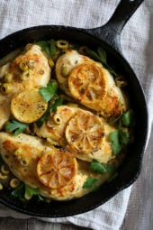 Chicken breasts cooked in a skillet with green olives, lemon and fresh herbs.
