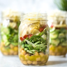 A quick and easy salad in a jar made with shaved Brussels sprouts, chickpeas, marinated artichokes, sun dried tomatoes and Asiago cheese. Perfect to pack for work or anywhere you need a portable lunch on-the-go! To serve you simply shake it up and pour it into a bowl.