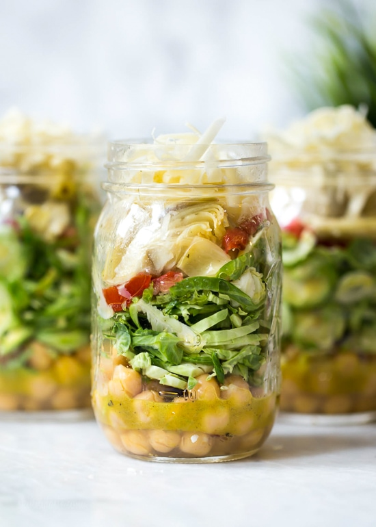 A quick and easy lunch solution for the week – salad in a jar made with shaved Brussels sprouts, chickpeas, marinated artichokes, sun dried tomatoes and Asiago cheese. Perfect to pack for work or anywhere you need a portable lunch on-the-go! To serve you simply shake it up and pour it into a bowl.