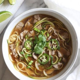 A quick, flavorful Vietnamese-inspired nood-less pho subs zucchini for rice noodles. So easy, the steak is sliced thin and cooks less than a minute in the ginger-garlic beef broth. Top this with fresh lime, basil, cilantro, jalapeno and scallions and you have one tasty soup!
