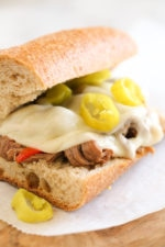 Set it and forget it with this easy slow cooker sandwich recipe. Top round roast, bell peppers, pepperoncini, garlic and dried herbs slow cooked all day then shredded and served on whole wheat Italian bread or rolls with melted provolone.
