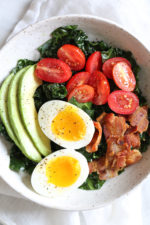 Salad for breakfast? Yes!! This Breakfast BLT Salad can be eaten anytime of the day really, but eggs and bacon served over this simple massaged kale salad with avocado and tomatoes is a delicious, savory, healthy breakfast idea.