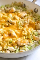 "Skillet Cheesy Chicken and Veggie ""Rice"" made with riced broccoli and cauliflower, sauteed chicken and cheddar cheese. I whipped this up for dinner the other night and my daughter loved it! It's so fast and easy to make I knew I had to share."