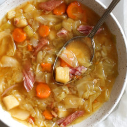 If you're making a big bone-in ham for the holidays this year, don't throw away the leftover ham bone once all the meat's been cut off. It's a key ingredient in this soup that adds instant flavor with minimal effort! Here I added some vegetables, potatoes and cabbage, there are no beans but you can add some if you wish. So delicious and easy to make!