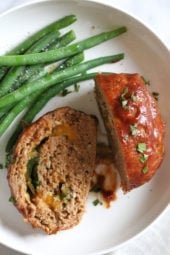 The best tasting, moist turkey meatloaf stuffed with cheddar cheese, spinach and rolled, jelly roll style topped with a ketchup based glaze.