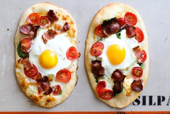 This easy, homemade breakfast pizza is made with bacon, eggs, tomatoes, spinach and cheese, made completely from scratch and ready in less than 30 minutes start to finish!